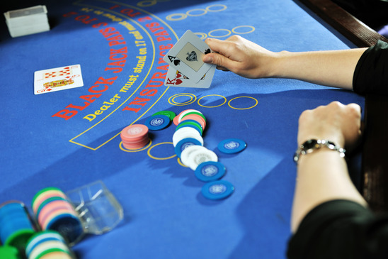 woman play black jack card game in casino